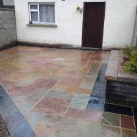 Sandstone paving (camel dust) with black limestone boarder
